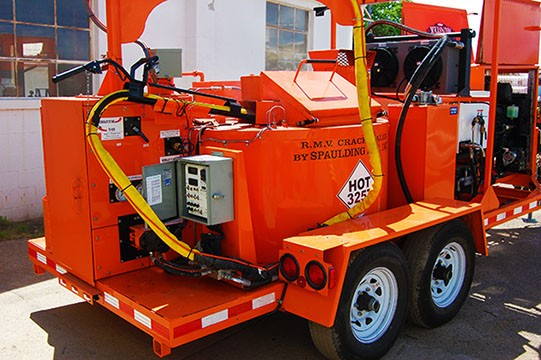 Large orange equipment with yellow hoses