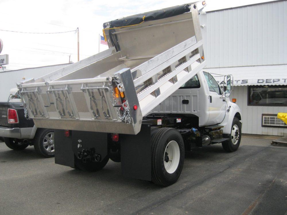 Aluminum dump truck body hoisted
