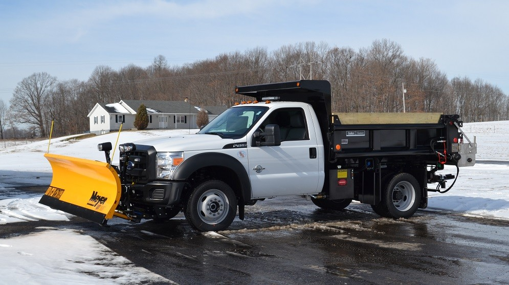 Truck with snowplow attached in parking lot
