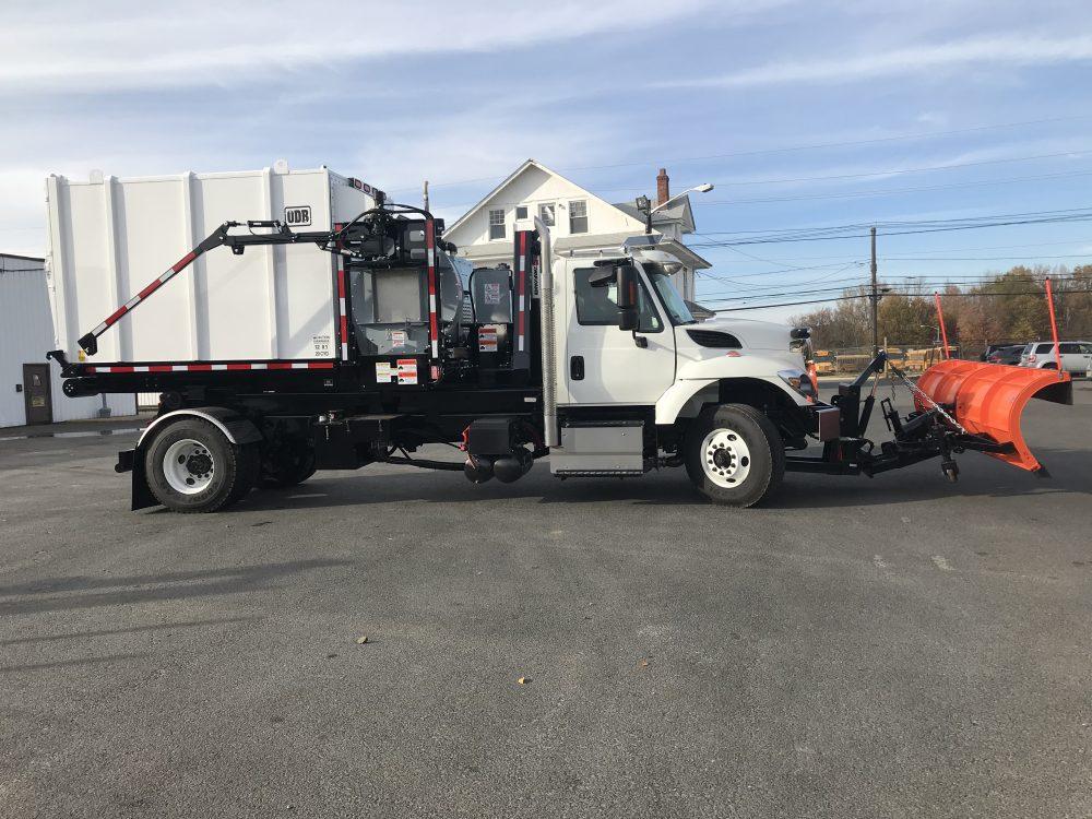 White hooklift truck in parking lot