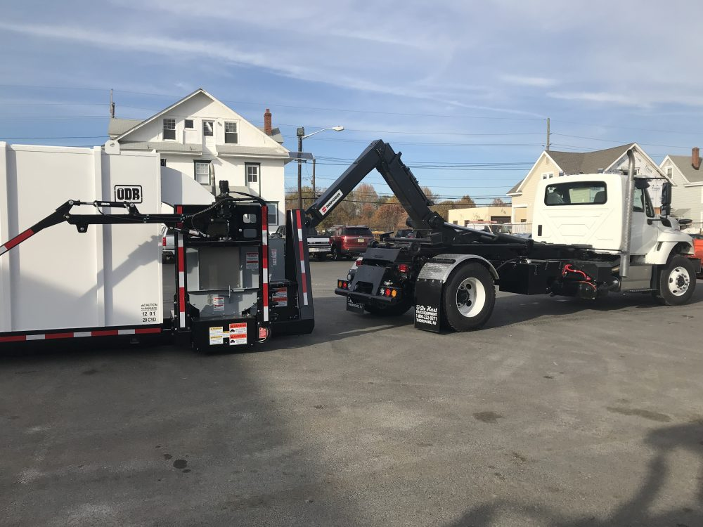 Right side view of white hooklift truck in parking lot