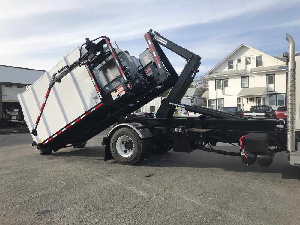 Side view of white hooklift truck in parking lot