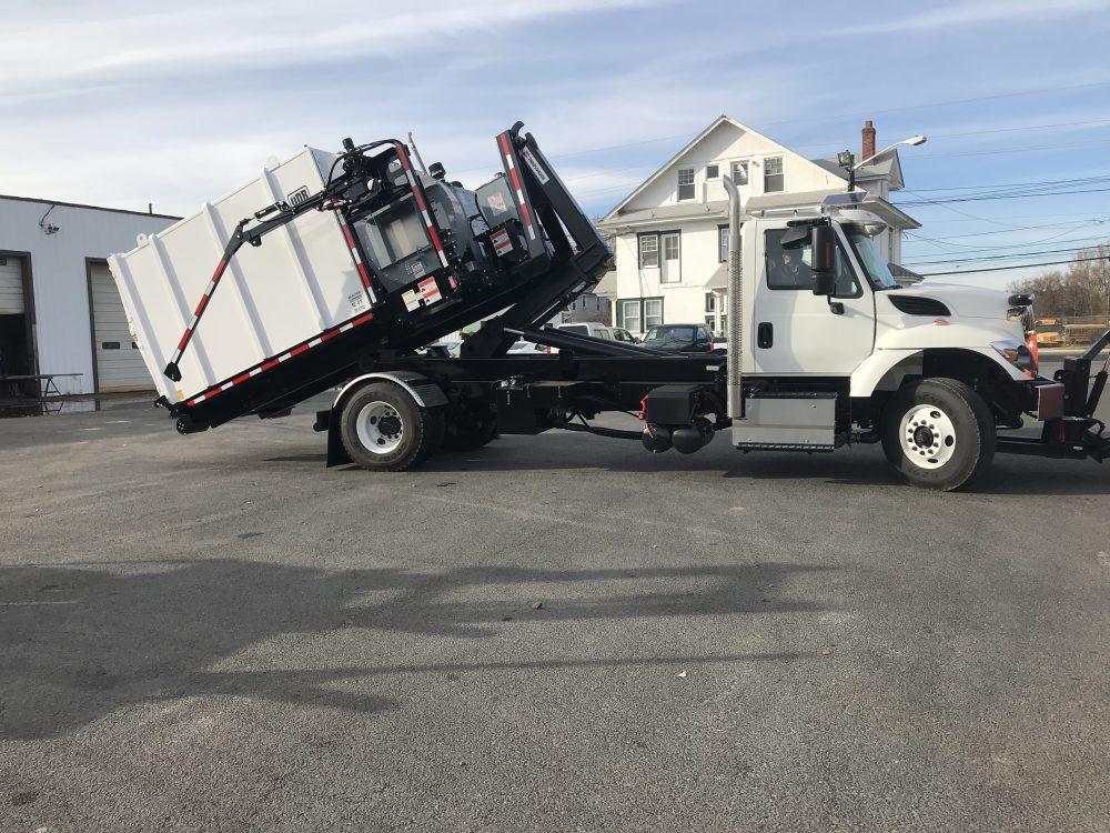 Side of white hooklift truck in parking lot