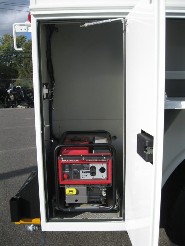 Opened compartment on truck showing generator
