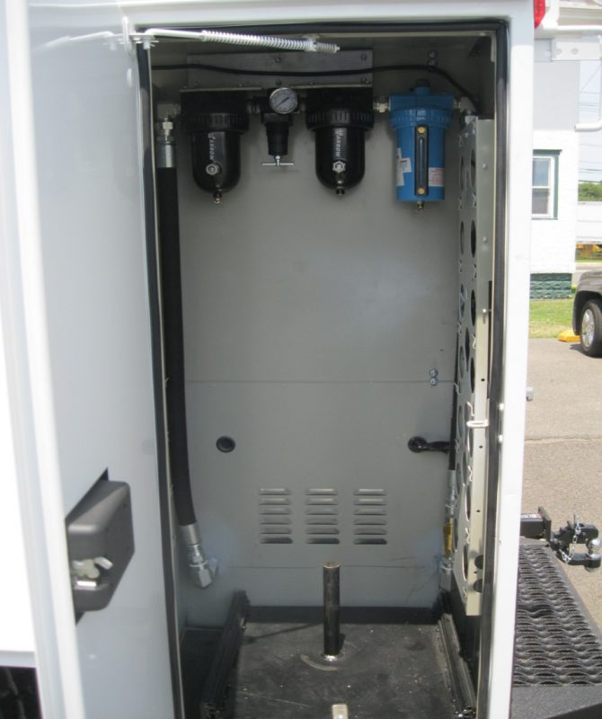 Opened compartment on truck showing equipment inside