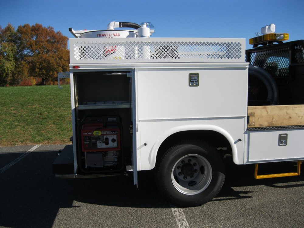 Side compartment of utlity truck showing pump