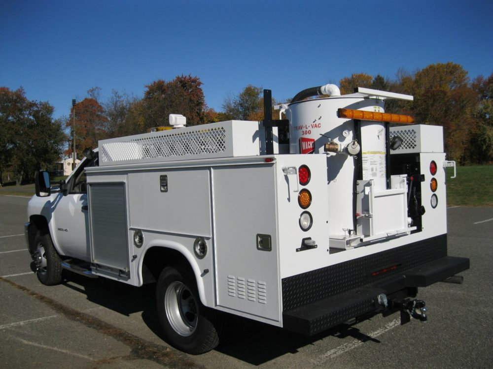 Side back view of white utility truck with equipment