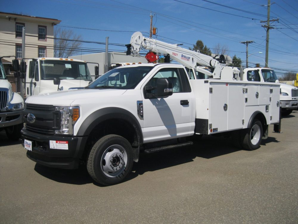 Front left view of white pickup truck with crane on back