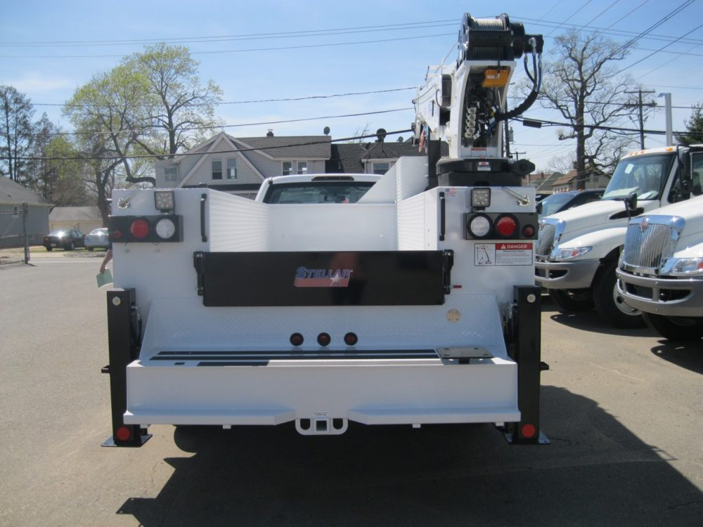 Rear view of white pickup truck with crane on back