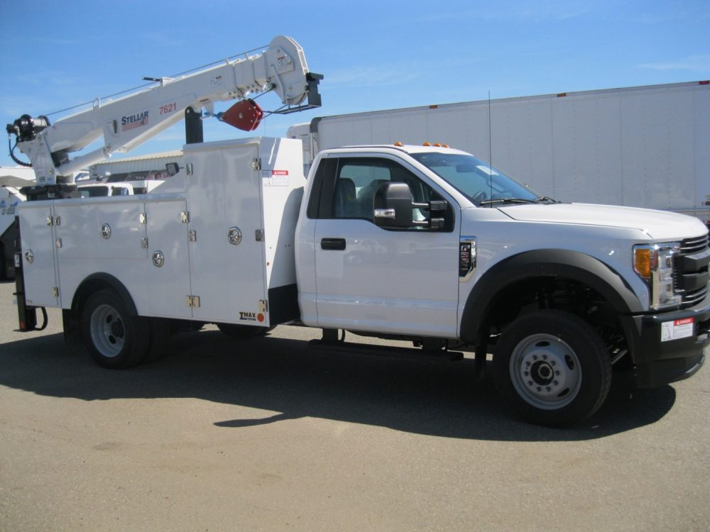 Front left side view of white pickup truck with crane on back