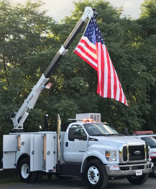 Utility truck with crane holding up American flag
