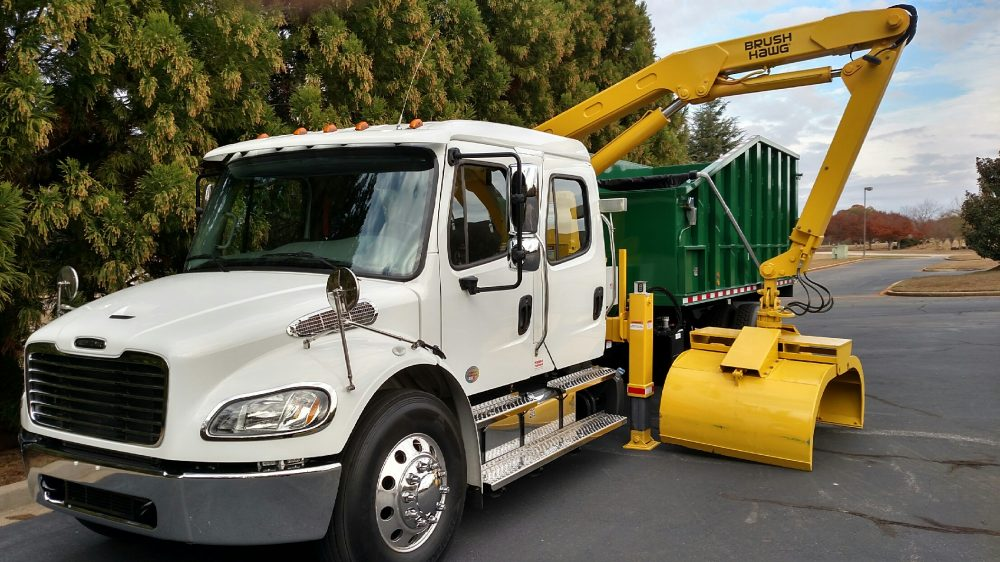 White semi truck with yellow equipment over green truckbed