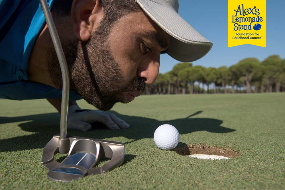 Humorous photo of man trying to blow a golf ball into the hole